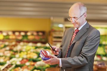 Deutschland, Köln, Mann mit Johannisbeer- und Mobiltelefon im Supermarkt