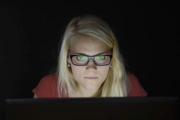 Junge Frau mit Laptop in der Nacht