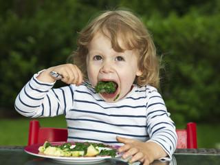 Deutschland, Düsseldorf, Mädchen draußen sitzen und essen Spinat