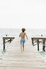 Spanien, Junge auf Steg läuft am Meer