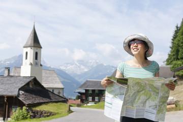 Österreich, Junge Frau mit Wanderkarte