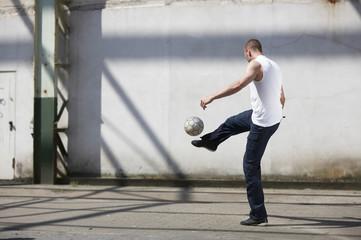 Mann spielt Straßenfußball