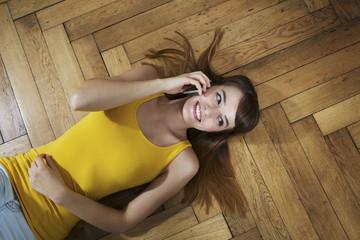 Deutschland, Berlin, junge Frau auf dem Boden liegend und mit Smartphone