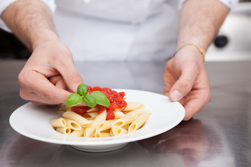 Chef Adding Fresh Basil to Plate of Pasta