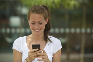 Deutschland, Köln, junge Frau mit Smartphone