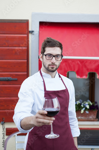 Chef holding a glass of red wine..