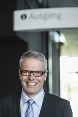 Deutschland, Stuttgart, Geschäftsmann stehend in Bürogebäude