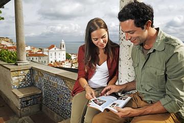 Portugal, Lissabon, Alfama, Miradouro de Santa Luzia, junges Paar mit Reiseführer