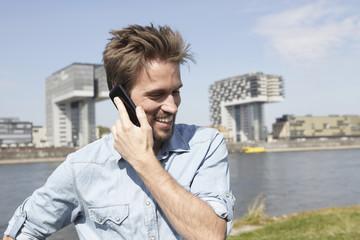 Deutschland, Köln, Mann, der auf Handy spricht