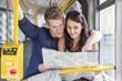 Polen, Warschau, Junges Paar im Bus liest Stadtkarte
