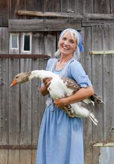 Deutschland, Bayern, Seniorin mit Gans auf dem Bauernhof