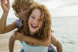 Spanien, Mädchen trägt Junge auf Schultern