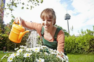 Deutschland, Köln, Junge Frau Blumen gießen