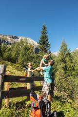 Österreich, Salzburg, Mutter hebt Sohn zu Vater über Zaun