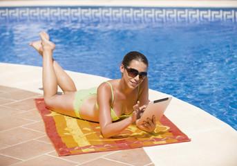Spanien, junge Frau, mit Tablet PC am Pool