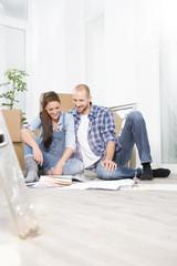 Junge Paare, die in neues Haus umziehen, Blick auf Farbmuster