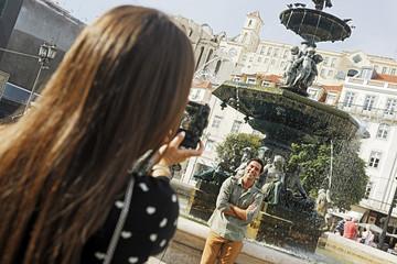 Portugal, Lissabon, Baixa, Rossio, Praca Dom Pedro IV, junges Paar fotografiert vor einem Brunnen