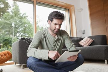 Deutschland, Nürnberg, Mann mit Tablet PC im Wohnzimmer