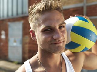 Deutschland, Düsseldorf, Junger Mann mit Volleyball im Industriegebiet