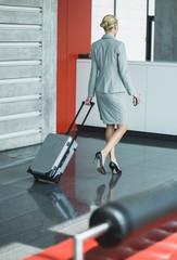 Deutschland, Stuttgart, Geschäftsfrau zu Fuß mit Rollkoffer
