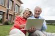 Deutschland, Nürnberg, Senior Paar mit Laptop im Garten