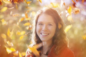 junge Frau mit wirbelnden Herbstblättern um sie herum