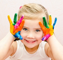 Cute smiling little girl with hands in paint