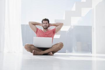 Spanien, Mann sitzt auf dem Boden mit Laptop
