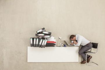Geschäftsmann schlafen auf Schreibtisch mit Stapel von Aktenordner
