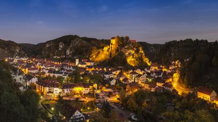 Deutschland, Bayern, Blick auf die Burg Pottenstein auf der Berg mit der Stadt im Vordergrund bei Nacht
