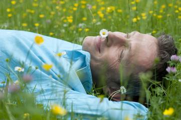Deutschland, Bayern, München, Mann entspannt im Garten
