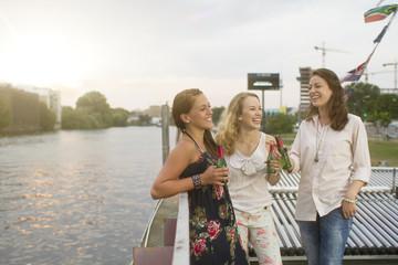 Deutschland, Berlin, Junge Studenten genießen Drink an Spreeufer Fluss