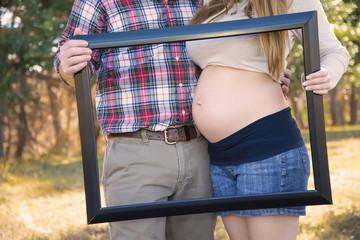 USA, Texas, Mann und Frau hält Bilderrahmen vor Bauch