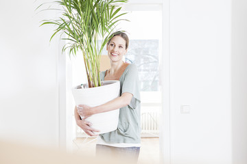 Frau mit Topfpflanze