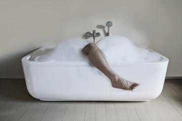 Mann in der Badewanne mit Bein