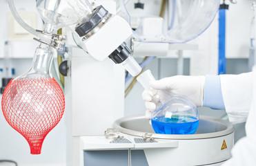 Deutschland, Junge Wissenschaftler untersuchen blaue Flüssigkeit auf einem Rotationsverdampfer