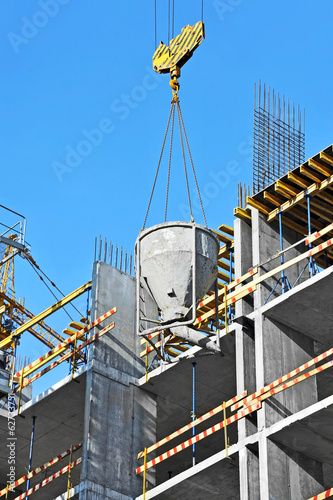 Crane lifting concrete mixer container on constructoin site