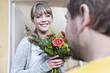 Deutschland, Köln, Junge Frau, die Blumen vom Briefträger