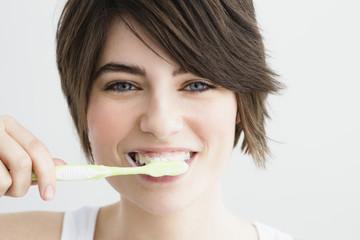 Deutschland, München, junge Frau beim Zähneputzen