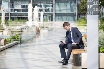 Deutschland, Hannover, Geschäftsmann mit Smartphone