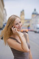 Deutschland, Bayern, München, junge Frau mit Smartphone vor Bayerische Staatsbibliothek in der Ludwigstraße