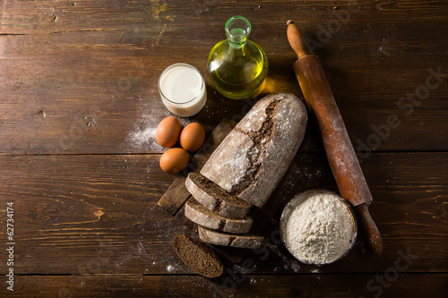 Still life photo of bread and flour with milk and eggs at the wo