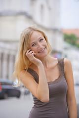 Deutschland, München, Junge Frau am Telefon vor der Ludwig-Maximilians -Universität