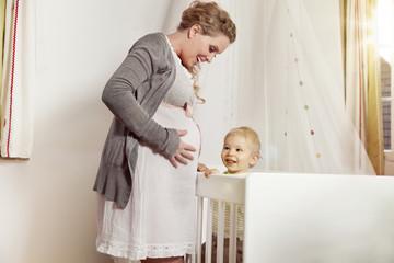 Deutschland, Bonn, Schwangere Mutter mit Sohn steht neben seinem Bett