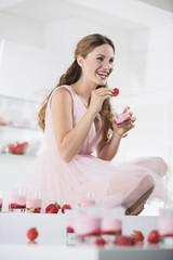 Deutschland, Junge Frau mit Gläser Erdbeer-Joghurt