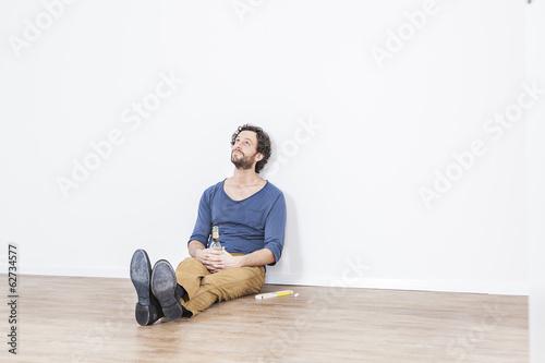 Mann sitzt auf dem Boden