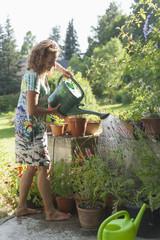 Deutschland, Bayern, München, Seniorin gießen von Pflanzen