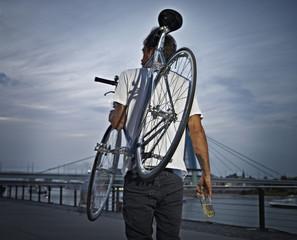 Deutschland, Köln, junger Mann trägt Fahrrad auf der Schulter