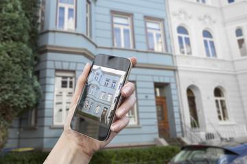 Deutschland, Bonn, Hand hält Smartphone- Anzeige zeigt historische Haus im Hintergrund