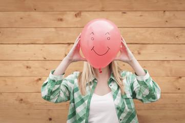 Deutschland, Jugendliche verdeckt Gesicht mit Smiley Ballon